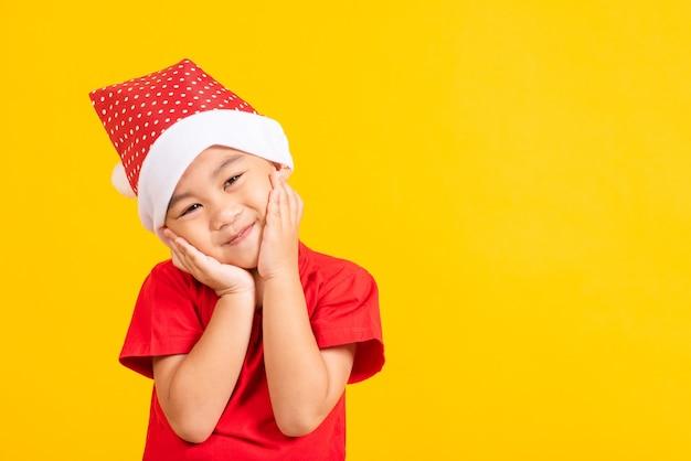 Los niños pequeños vestidos con sombrero rojo de papá noel conmocionado usan el concepto de la cara del asimiento de la mano del día de fiesta de navidad