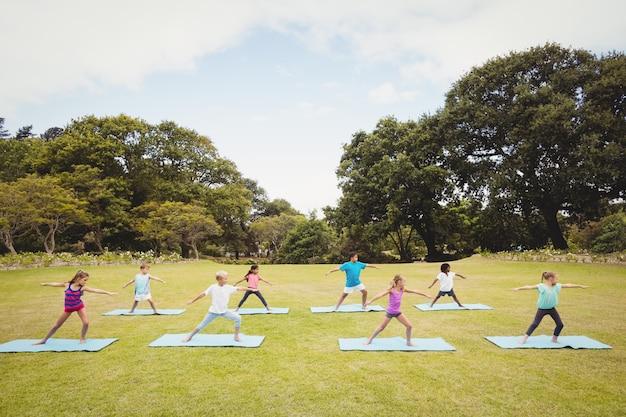 Niños de pie y haciendo yoga
