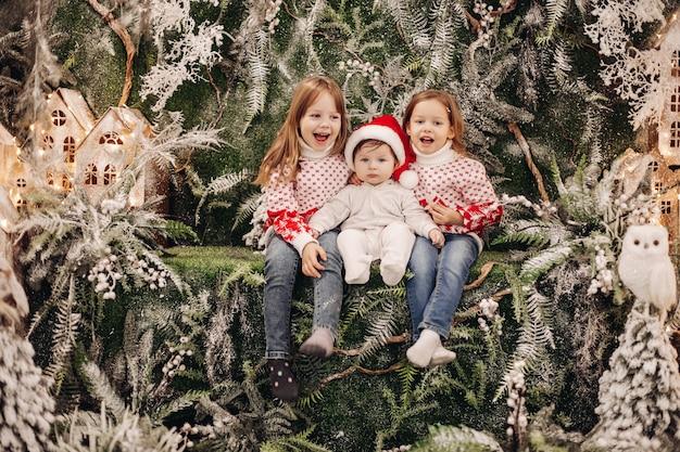 Niños de pie en el nivel superior de la decoración navideña.