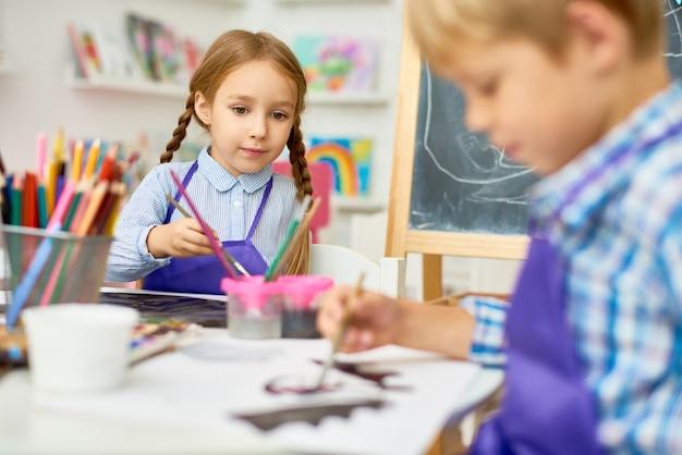 Niños pintando en la clase de arte de la escuela de desarrollo