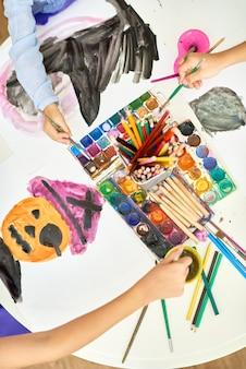 Niños pintando cuadros de halloween en art studio