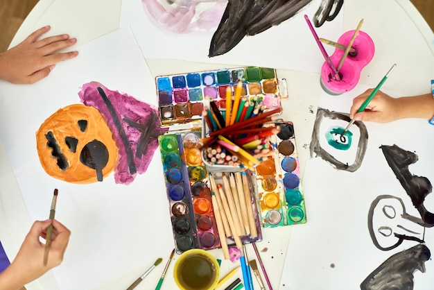 Niños pintando cuadros de halloween en clase de arte