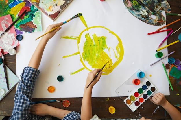 Niños pintando el sol sobre la vista