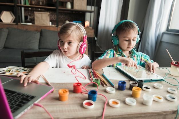 Niños pintando y usando ordenador