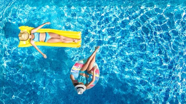Los niños en la piscina con vista de aviones no tripulados desde arriba, los niños felices nadan en un anillo inflable con donas y colchones, las niñas activas se divierten en el agua durante las vacaciones familiares en el complejo vacacional