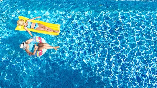 Los niños en la piscina con vista de aviones no tripulados desde arriba, los niños felices nadan en un anillo inflable con donas y colchones, las niñas activas se divierten en el agua en vacaciones familiares en un resort