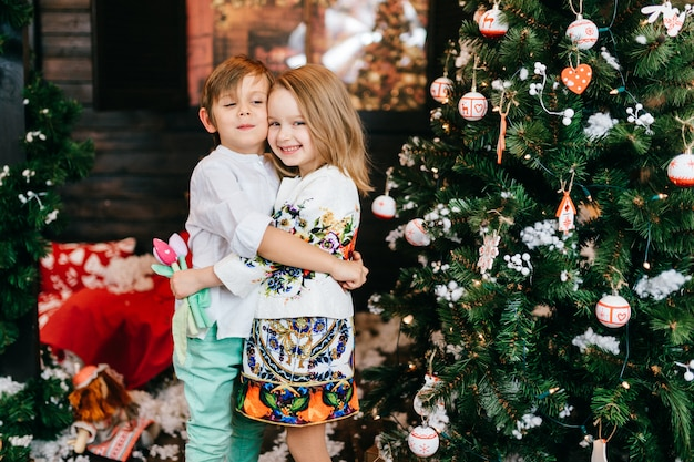 Niños positivos abrazando y sonriendo en estudio con árbol de cristmas y decoraciones de año nuevo.