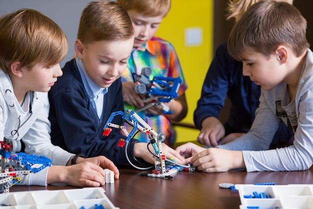 Los niños positivos juegan y ensamblan al constructor en la habitación de los niños.