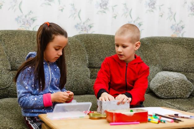 Niños de primaria niño y niña dibujando en casa