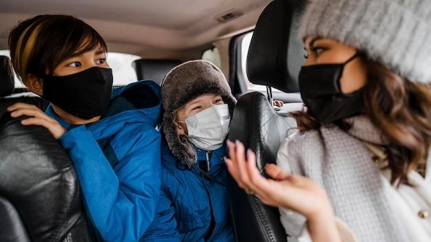 Niños de primer plano y mujer con máscaras