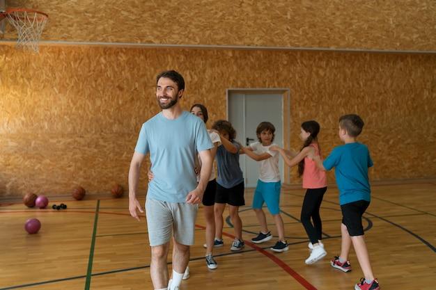 Niños y profesor de tiro completo en el gimnasio