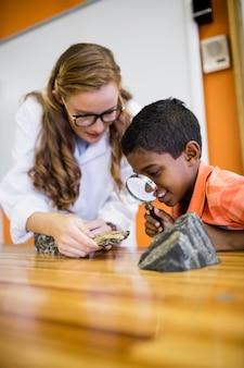 Niños que buscan fósiles con una lupa
