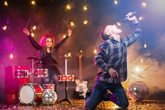 Los niños que fingen ser una banda de rock tocan y cantan