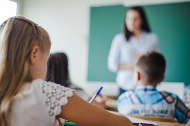 Niños que se sientan en aula en la lección