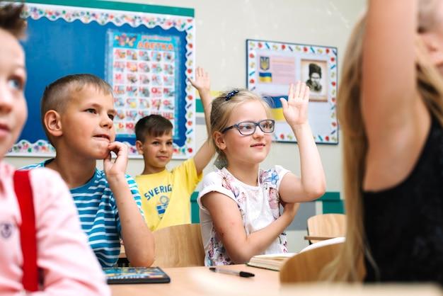 Niños que se sientan en los escritorios de la escuela que levantan las manos