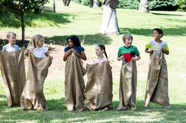 Niños que tienen una carrera de sacos en el parque