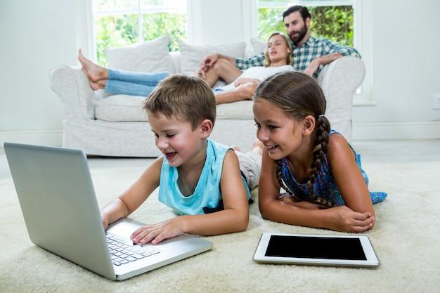 Niños que usan una computadora portátil frente a los padres en casa