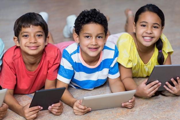 Niños que usan tabletas digitales mientras están acostados en el piso