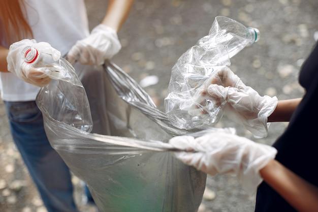 Los niños recogen basura en bolsas de basura en el parque