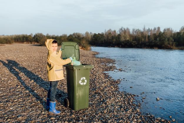 Niños recogiendo botellas vacías de plástico en una bolsa de basura, ayuda voluntaria.