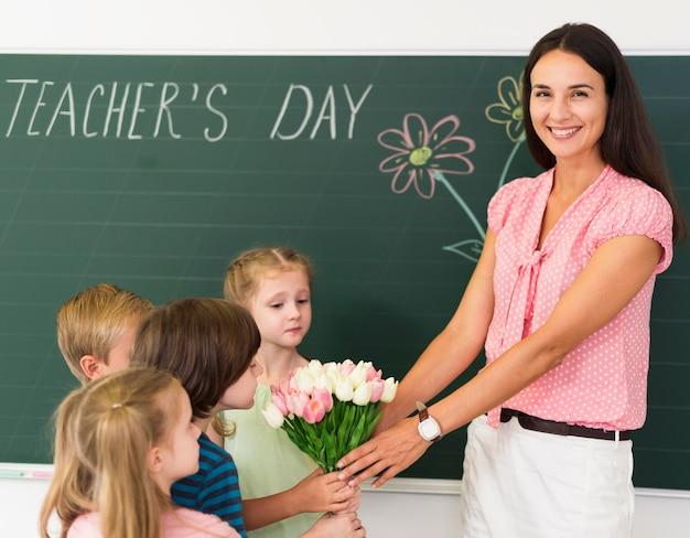 Niños regalando flores a su maestra.