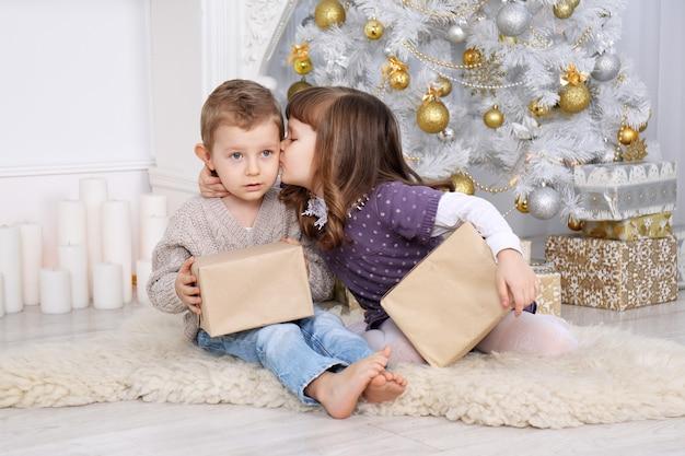 Niños con regalos bajo el árbol de navidad.