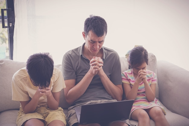 Niños rezando con el padre frente a la computadora portátil.