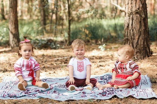 Los niños en la ropa ucraniana tradicional juegan en el bosque en rayo de sol. chico y dos chicas