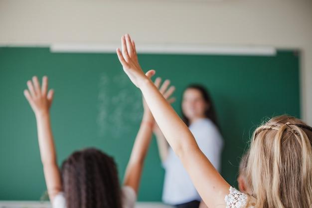 Niños en el salón de clase levantando las manos