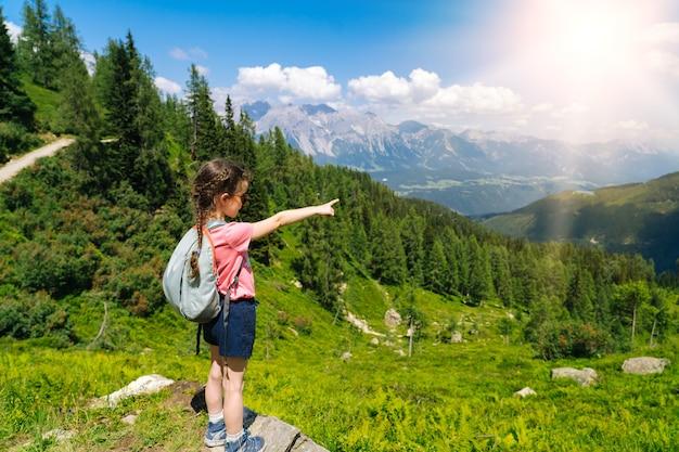 Los niños senderismo en un hermoso día de verano en las montañas de los alpes austria