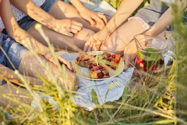 Niños sentados en el césped comiendo pastel casero con bayas, bebiendo bebida de fresa y menta
