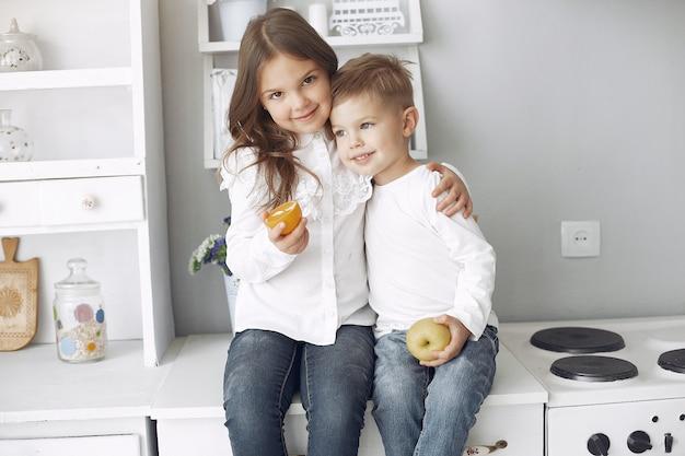 Niños sentados en una cocina en casa