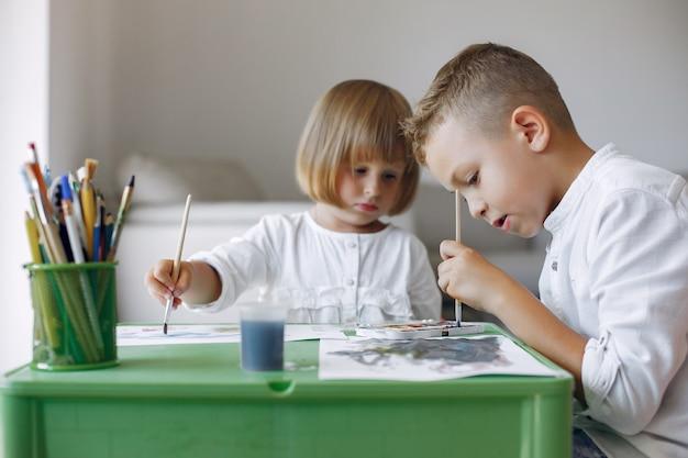 Niños sentados en la mesa verde y dibujando