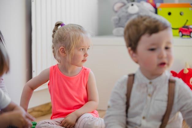 Niños sentados en el piso en la sala de juegos