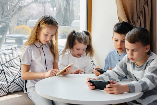 Los niños se sientan en una mesa en un café y juegan juntos teléfonos móviles. entretenimiento moderno