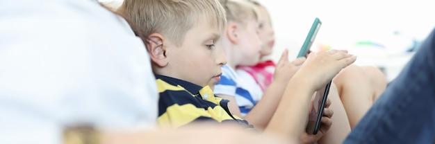 Los niños se sientan en el sofá y juegan en sus teléfonos inteligentes.