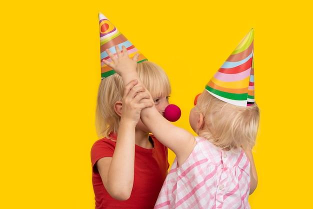 Niños con sombreros festivos y narices de payaso. vacaciones para niños. niños de cumpleaños.
