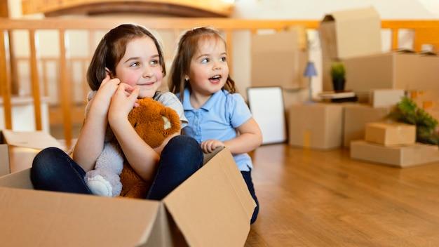 Niños sonrientes con caja y juguetes.