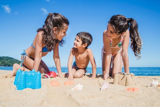 Niños sonrientes jugando en la playa