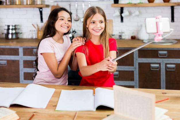 Niños sonrientes sentados en el escritorio y tomando autofotos en la cocina