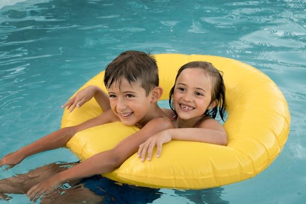 Niños sonrientes de tiro medio con aro salvavidas