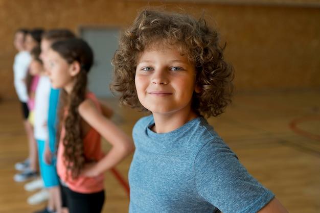 Niños sonrientes de tiro medio en el gimnasio de la escuela
