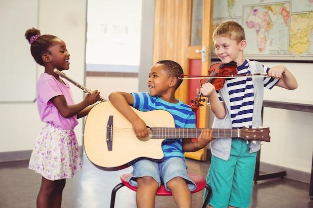 Niños sonrientes tocando la guitarra, el violín, la flauta en el aula