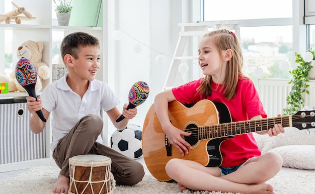Niños sonrientes tocando el tambor y la guitarra