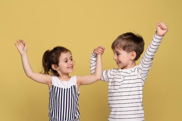 Niños sonrientes tomados de la mano