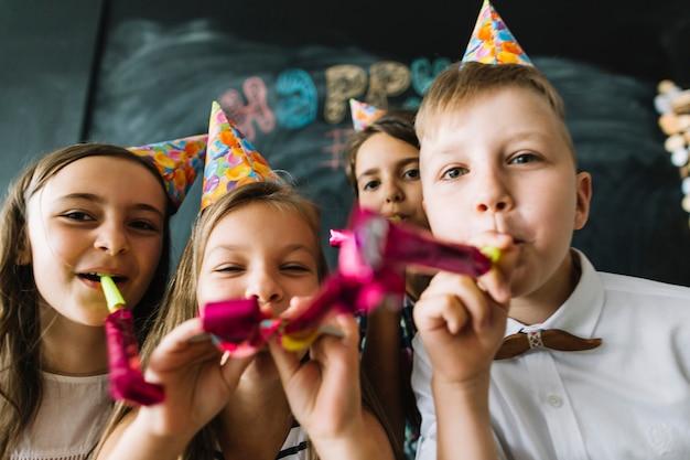 Niños soplando cuernos de fiesta a la cámara juntos
