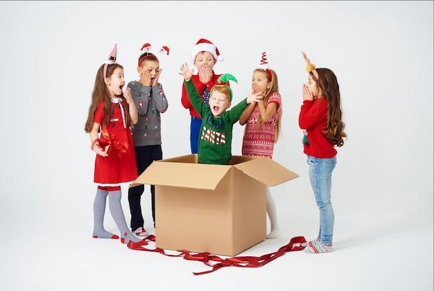 Los niños se sorprenden al abrir el regalo de navidad.
