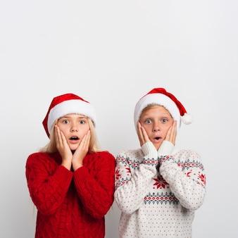 Niños sorprendidos con sombreros de santa
