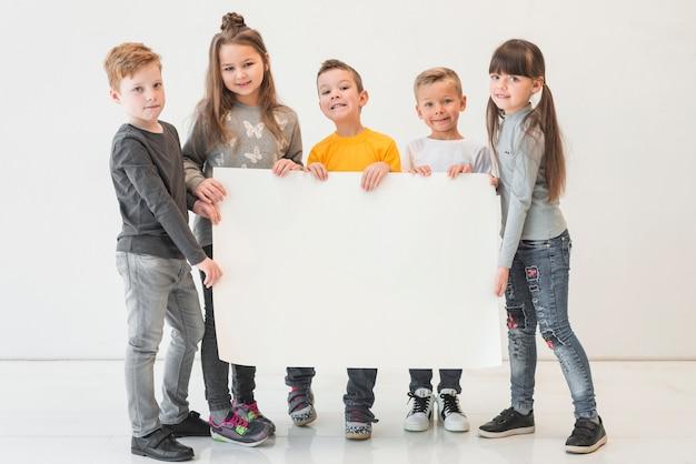 Niños sosteniendo cartel vacío