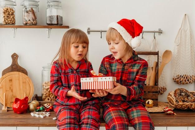 Niños sosteniendo juntos un regalo de navidad